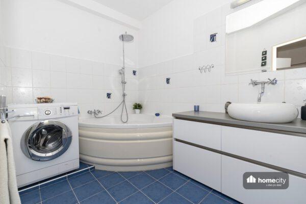 Fotografie koupelny s rohovou vanou, pračkou a umyvadlem